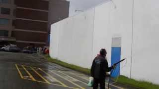 De greasing and washing a factory wall in preparation for painting