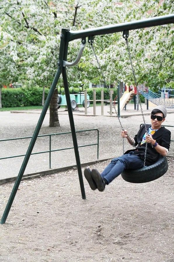 Bryanboy in Jil Sander on a playground swing in Sodermalm, Stockholm