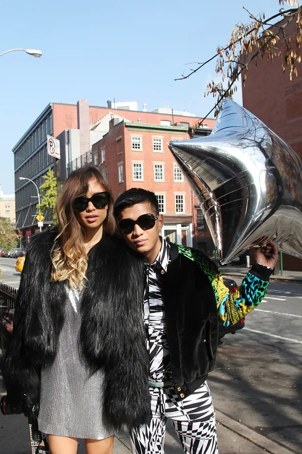 Rumi Neely and Bryanboy holding a silver star balloon on the street