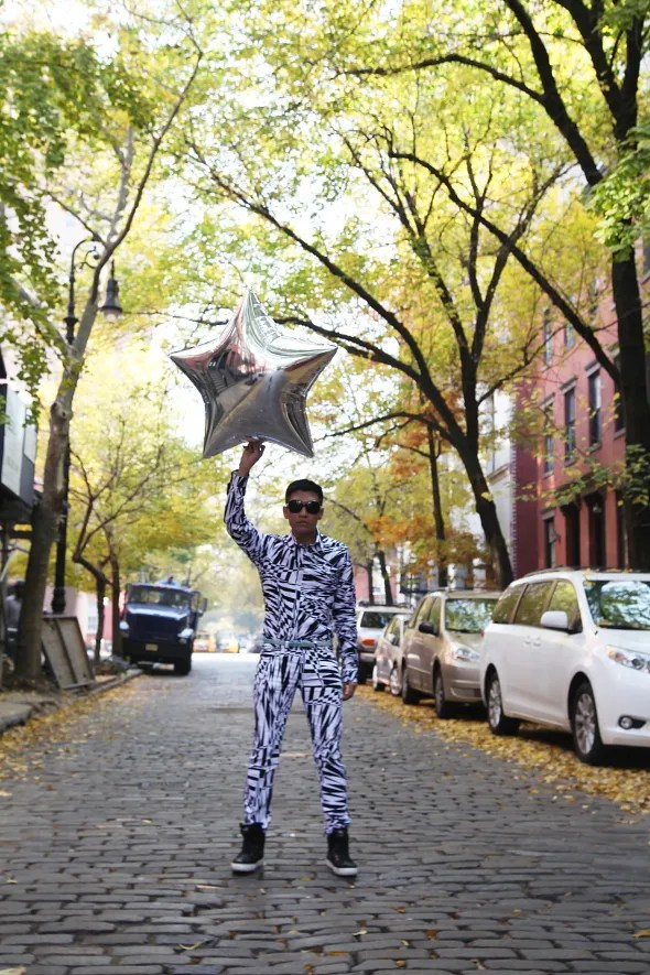 Bryanboy with a silver star balloon on Jane Street, New York City