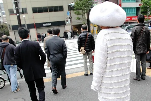 White hat and white coat on the street