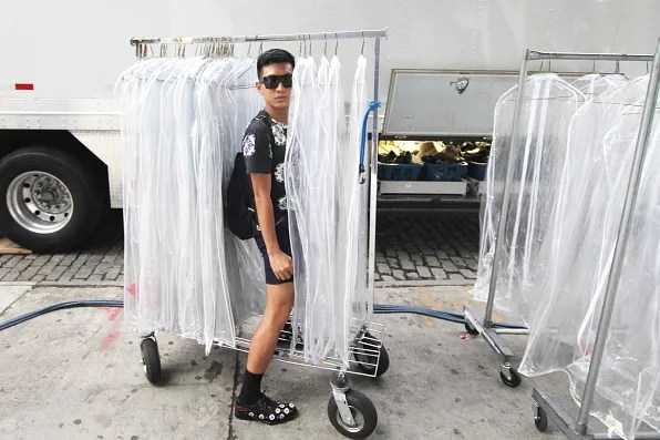 Bryanboy with an empty rack of garment bags