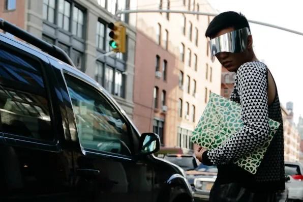 Bryanboy outside Cafe Select wearing Alexander McQueen visors