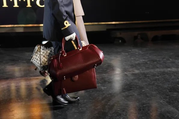A porter carrying Louis Vuitton bags