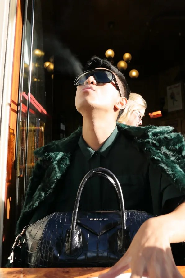 Bryanboy smoking a cigarette at a cafe in Paris' Marais district
