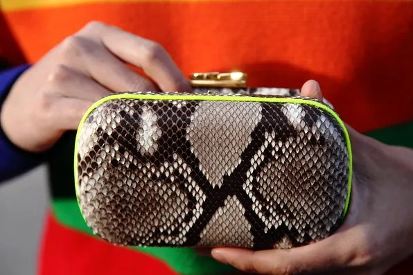 Snakeskin clutch bag by Corto Moltedo and gold Michael Kors watch