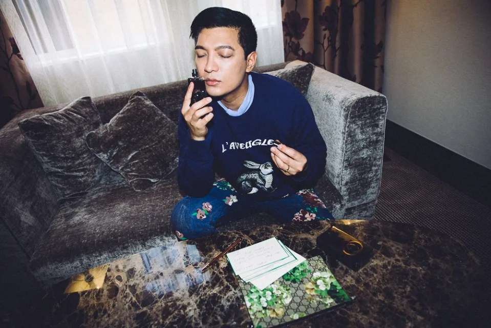 Fashion blogger Bryanboy holding a Gucci Guilty fragrance bottle in London