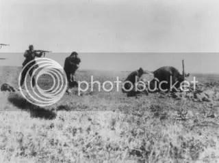 """Soldado alemán apunta, con ademan de disparar, a una mujer que lleva a su hijo en brazos, al cual intenta proteger. A la derecha, unos hombres parecen cavar la que sera su tumba. La imagen fue enviada por un soldado alemán a su familia via correo, pero esta fue interceptada por trabajadores del servicio postal polaco. En el reverso de la fotografía reza: """"Ucrania 1942, Campaña contra los Judíos, Ivangorod"""". Frente del Este, Segunda Guerra Mundial."""
