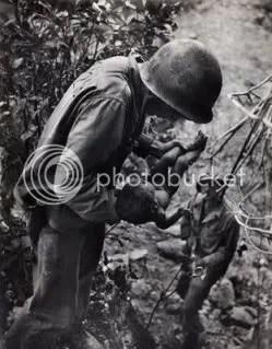 Un marine encuentra a un niño herido en la isla de Saipán (Islas Marianas). En la Batalla de Saipan se enfrentaron el ejercito de los Estados Unidos y el Ejercito Imperial Japones dentro del marco de la Guerra del Pacífico, correspondiente a la Segunda Guerra Mundial. Imagen tomada por W. Eugene Smith en 1944.