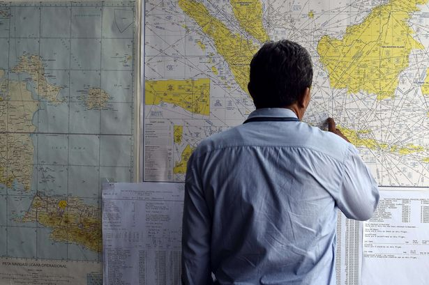 A man looks at a map showing the search area for missing Malaysian air carrier AirAsia flight QZ8501 outside the crisis-centre set up at Juanda International Airport
