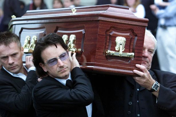 Lead singer of U2 Bono helps carry his father Bob Hewson's coffin