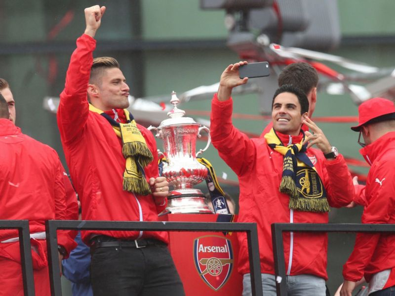 Olivier Giroud and Mikel Arteta celebrate with the FA Cup during the parade