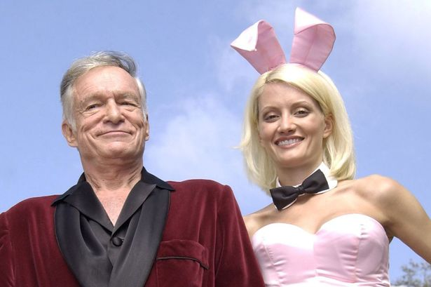 "Playboy founder Hugh Hefner and Playboy bunny Holly Madison perform a scene during the filming of a commercial for ""X Games IX"" at the Playboy Mansion May 6, 2003 in Holmby Hills, California"