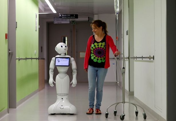 "A woman walks with new recruit ""Pepper"" the robot"