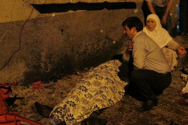 A man and a woman mourn next to a body of one the victims of a blast targeting a wedding ceremony
