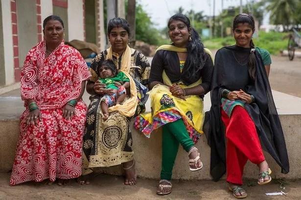 Anita Sambhaji Raut, 48, mother of the werewolf sisters and her five-month-old grandson with her daughters Manisha Sambhaji Raut, 22, (right) Savitri Sambhaji Raut, 19, (centre) and Laxmi Sambhaji Raut, 18, (left) at their residence in Maharashtra, India