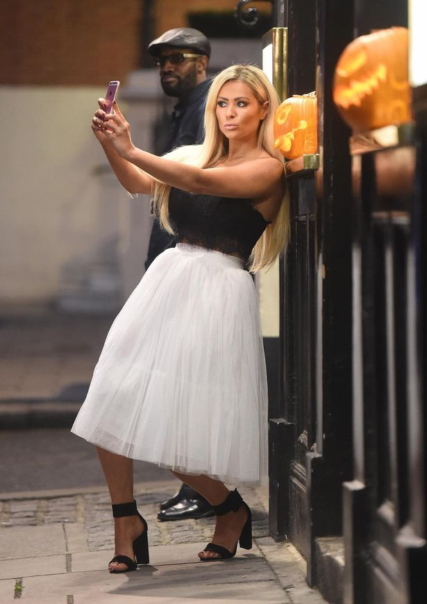 Model and TV personality Nicola McLean takes a selfie on her iPhone while out and about in London, United Kingdom. Nicola was looking stylish in a lace crop top and flared tulle skirt, paired with black heels