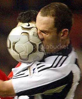Image of fottballer eing hit in face with football.