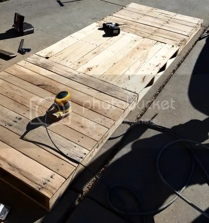 Building a child-sized table with pallet wood for an outdoor birthday party.