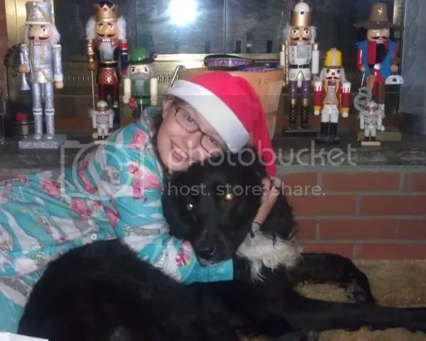 Girl in Santa Hat in front of Nutcracker collection with black dog.