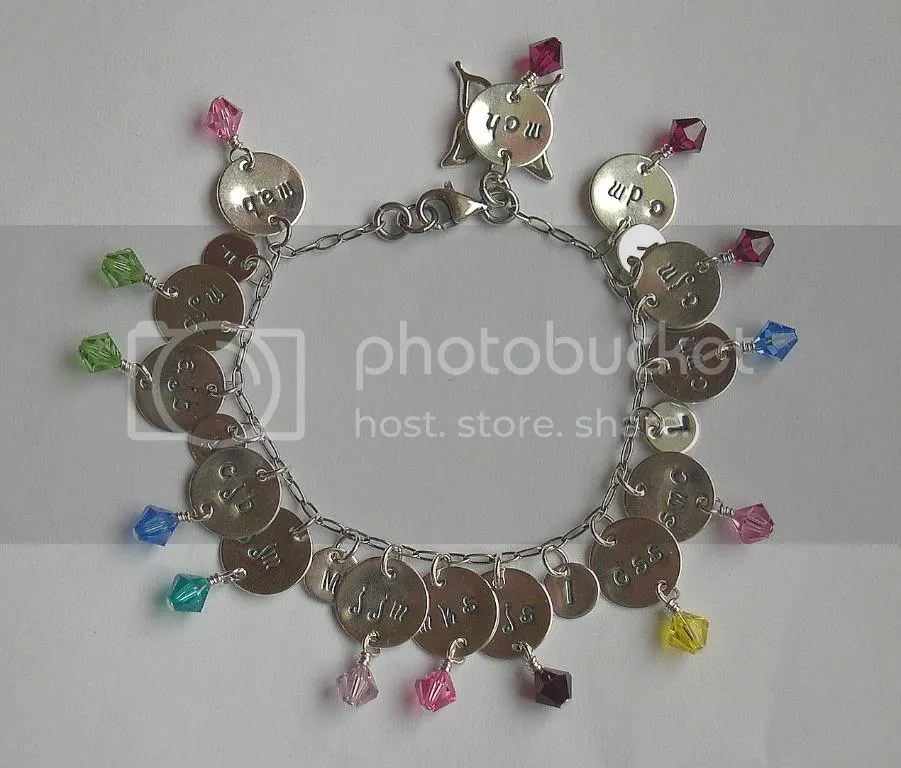 The family bracelet.  This is a version of a bracelet I originally designed for my mother.  In this piece, each monogram charm represents one of the recipients children or grandchildren, with a birthstone crystal dangle.  Throughout the bracelet on smaller discs are letters that spell out family.