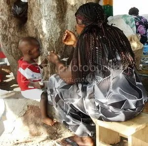 An African woman feeding her child at the Dodi island boarding area.