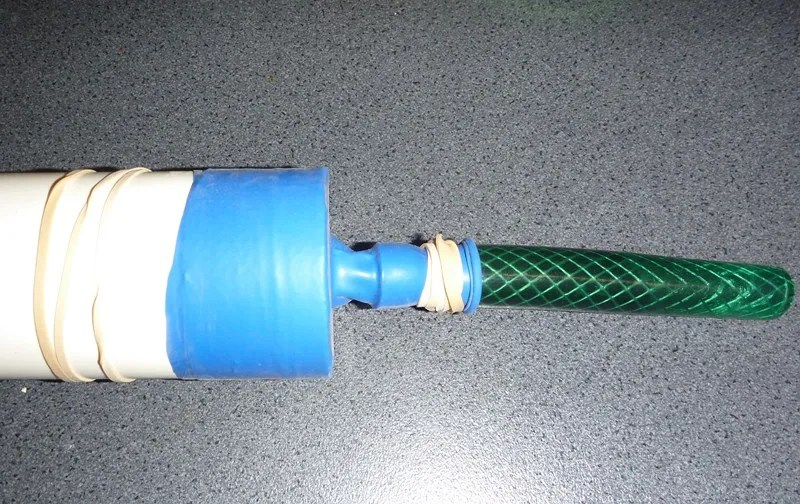 Elastic band and balloon on end of PVC pipe