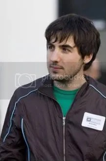 Geek: check. Hair in eyes: check. Out of place track jacket: check.