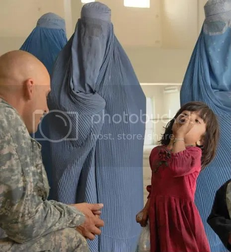 U.S. Army troop soldier talks with Afghan child