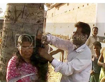 Public act of humiliation as woman is tied to tree and hair is shaved.
