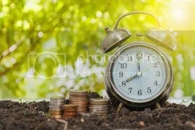 Alarm Clock And Money coins Stack And Alarm Clock On Background by jk1991