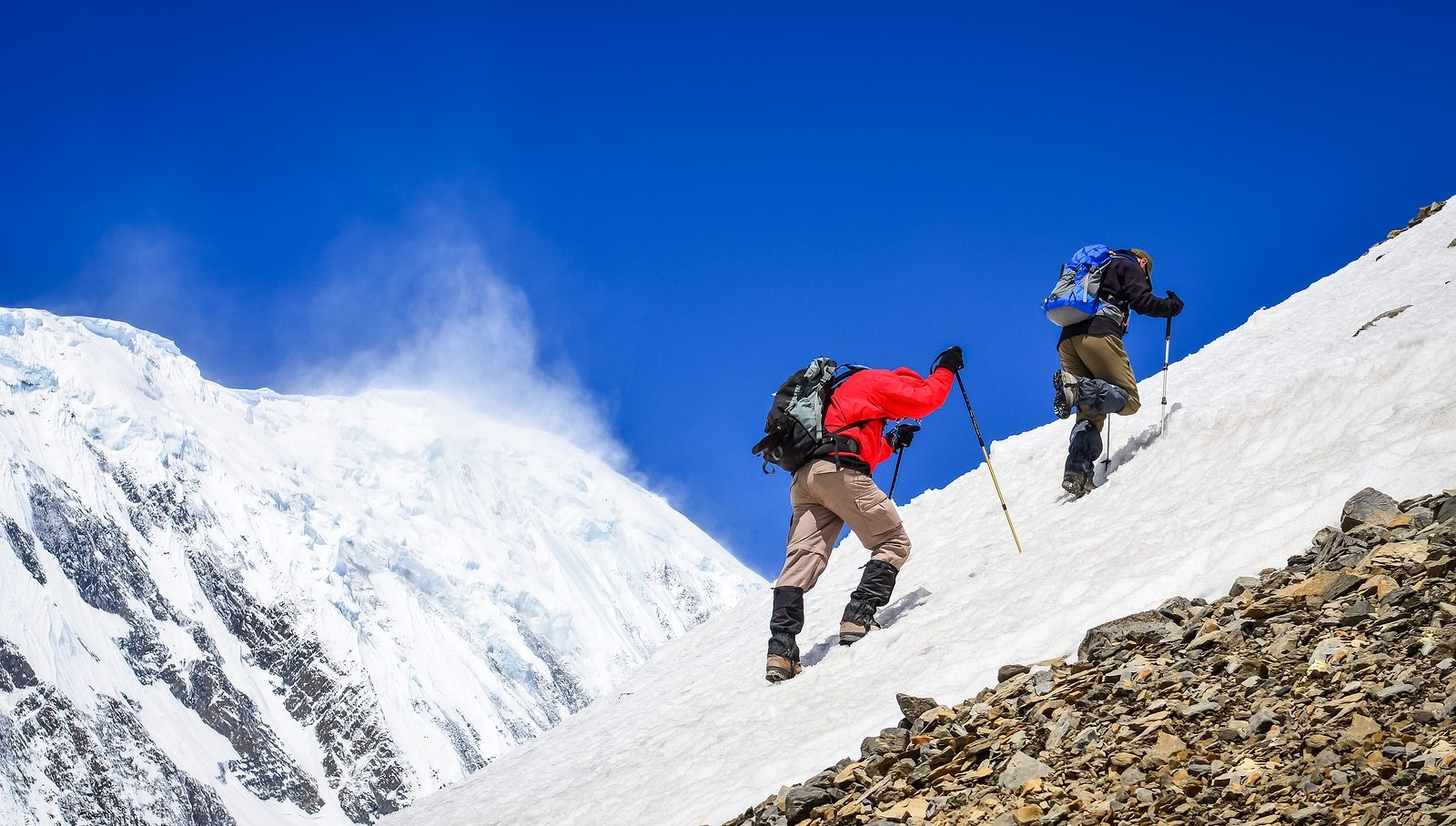 Two mountain backpackers walking on snow with peaks background Himalayas