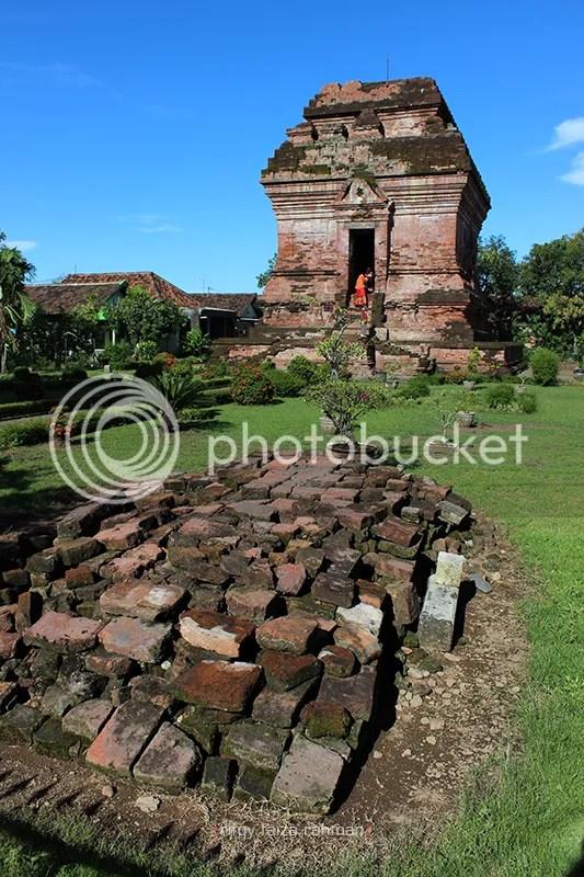 Batu berserakan di barat candi.Menurut Sahroni, reruntuhan tersebut merupakan pondasi gapura,yang satu sisinya kini dibangun pos jaga tempatnya bertugas.