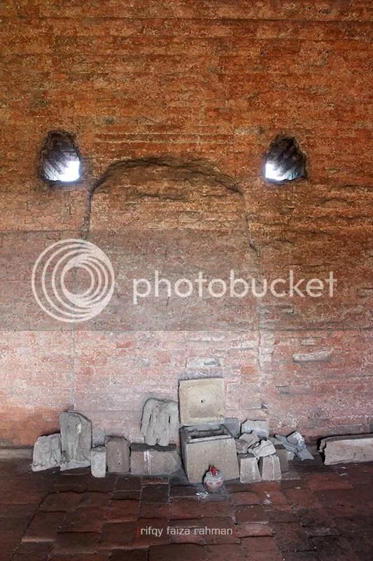 Tempat peribadatan di dalam candi.Tampak tonjolan dinding bekas pelinggihan arca berukuran besar, arca-arca tanpa kepala, kotak peripih, dan dupa. Terlihat pula dua di antara enam lubang sirkulasi udara yang melekat di dinding candi.