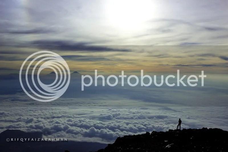 Siluet rekan setim menghadap Gunung Sindoro dan Gunung Sumbing yang bersandingan di tengah gumpalan awan.