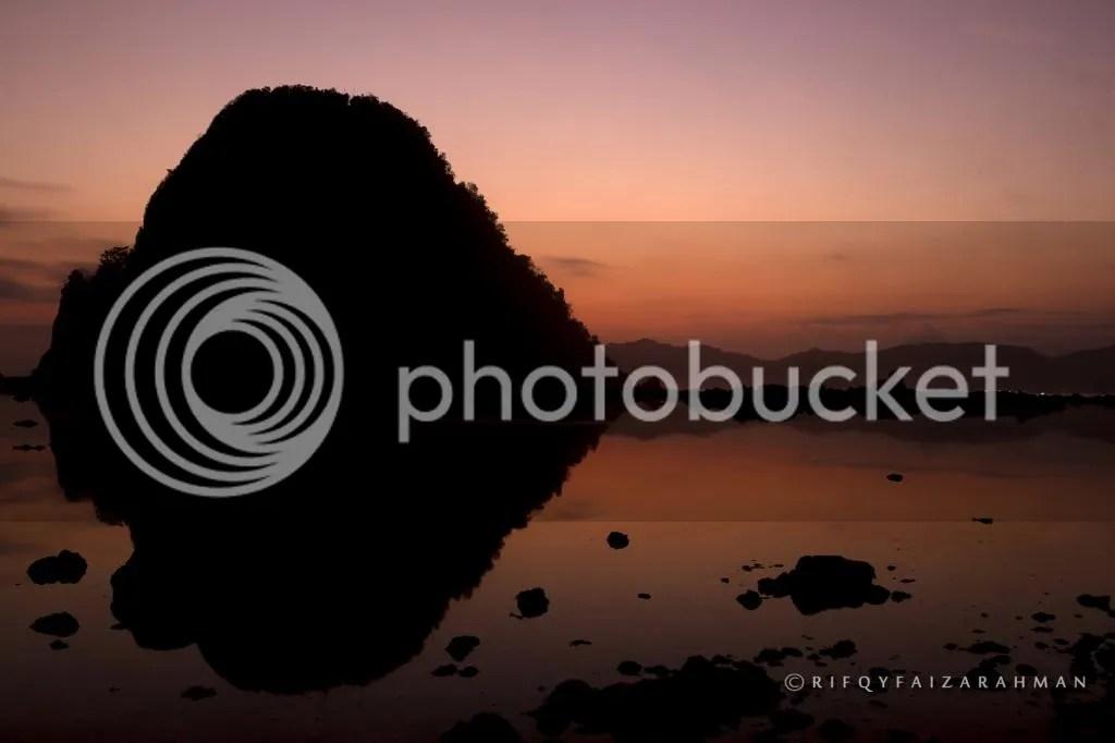 Siluet Pulau Merah yang berbayang di air laut yang surut saat sunset