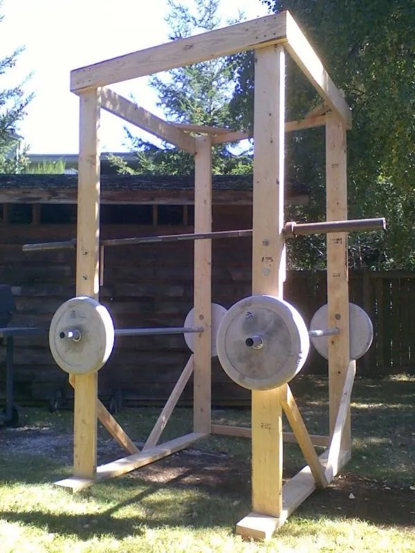Picture of DIY Squat rack made of dimensional lumber and concrete-cast bar weights.