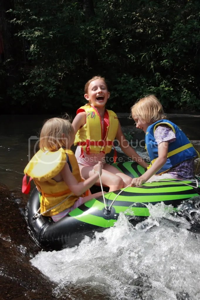 Three Girls Tubing in a light Whitewater, Smiling