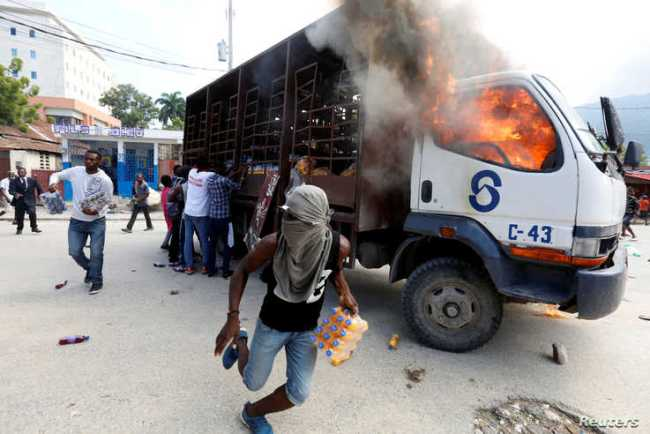Demonstrators loot a burning truck after the wake of demonstrators killed during the protests to demand the resignation of Haitian president Jovenel Moise in Port-Au-Prince, Haiti, Nov. 19, 2019.