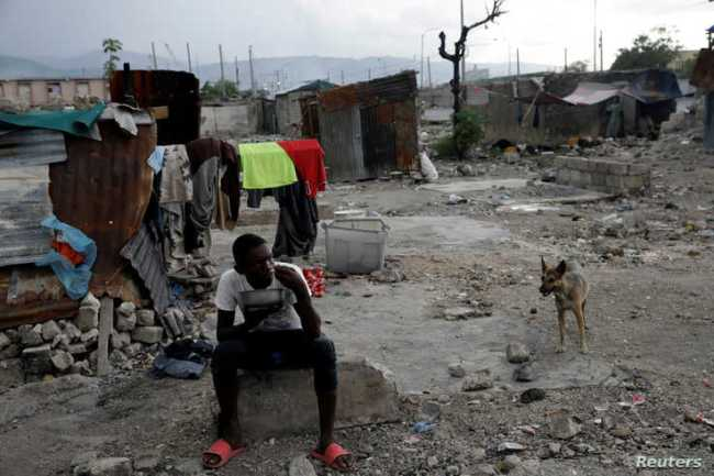 A boy eats next to makeshift shelters at La Saline neighborhood in Port-au-Prince, Haiti, Aug. 8, 2019.