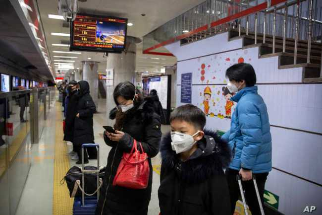 Passengers wear face masks as they wait for a train at a subway station in Beijing, Jan. 24, 2020.