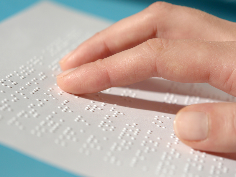 Fingers reading on a page of Braille