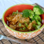orange painted bowl of honey seame chicken with green brocolli
