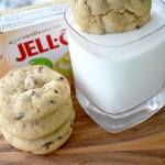 dunking pudding cookie into glass of milk with cookies next to glass