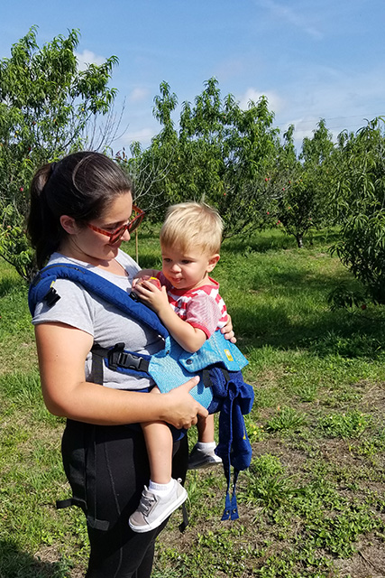 Boy in carrier on mothers chest eats a peach at farm
