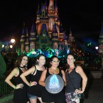 women pose in front of castle at disney villain night