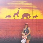Woman and small girl in front of safari type mural at Disney park