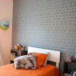 little boys bedroom with blue wall and orange bedspread