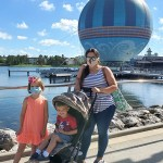 kids and mother at water edge with large balloon in background