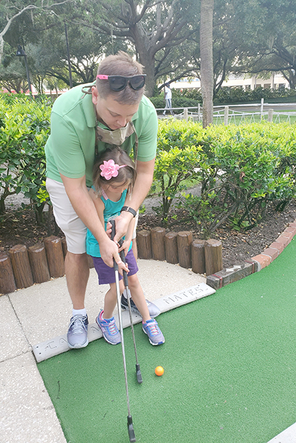 father and daughter putt at mini golf hole